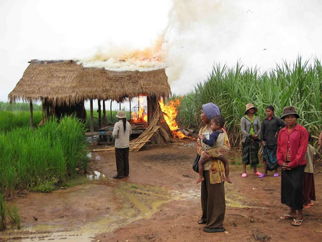 People watch a community building burn next to a sugar plantation belonging to Thailand's Mitr Phol Sugar Corporation in Oddar Meanchey after authorities set it ablaze during a 2009 eviction. Photo supplied