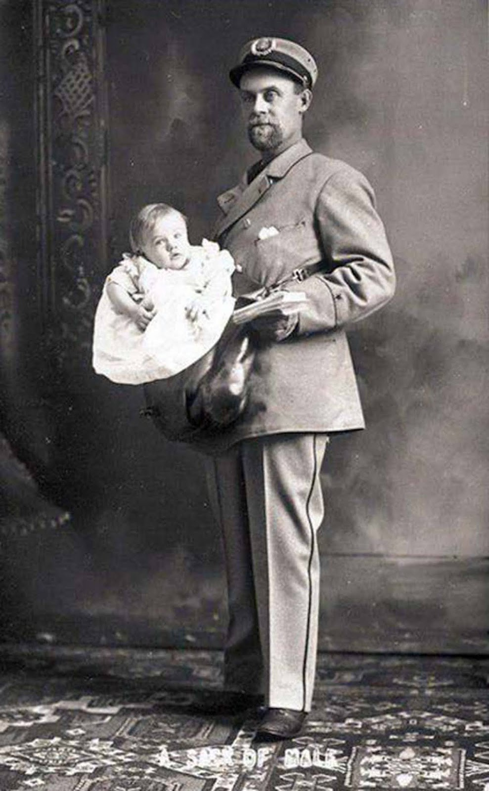 A US postman carrying a baby boy along with his letters, USA. 1900s.