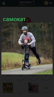 папа с ребенком на самокате катается в парке по дороге