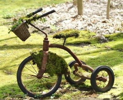 Siapkan sepeda roda tiga bekas yang sudah rusak, lalu cat dengan warna yang diinginkan supaya terlihat baru. Atau, biarkan warna sepeda tetap usang untuk memberi kesan rustic pada kebun.
