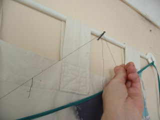 Wrapping the thread around a nail on the wall