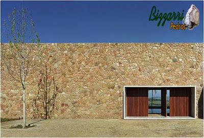 Construção de parede de pedra, com pedra moledo, tipo chapada com cantos, nessa cor de pedra amarelada, com espessura de 15 cm a 25 cm.