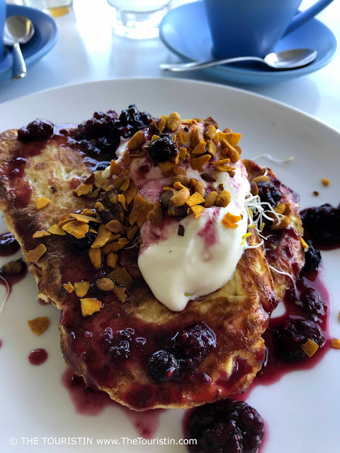 French Toast decorated with yoghurt, berry compote and honeycomb, served on a white plate.
