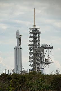 Falcon Heavy pod koniec grudnia 2017 roku został wytoczony pod stanowisko startowe 39A w Centrum Kosmicznym Kennedy'ego i postawiony do pionu przed planowanymi na połowę stycznia 2018 finalnymi przygotowaniami, testem statycznym i dziewiczym startem. Credits: Dave Borinski