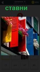 на доме в окнах сделаны цветные ставни в открытом виде