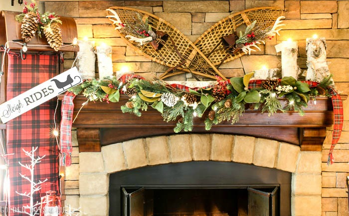 Christmas mantel with sleigh ride decor on stone fireplace with toboggan, garland and antique snow shoes