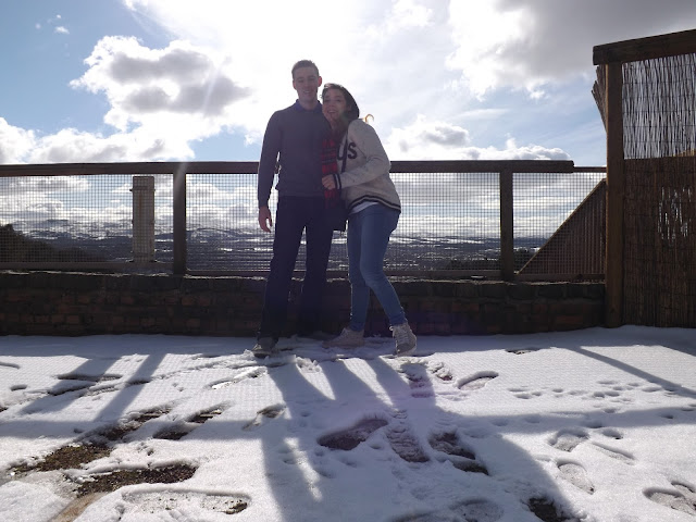 Two people standing in front of a scenic snowy viewpoint