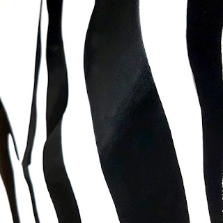 Surreal Painting of female body laying forward, created using black and white dripping stripes to reveal the body.
