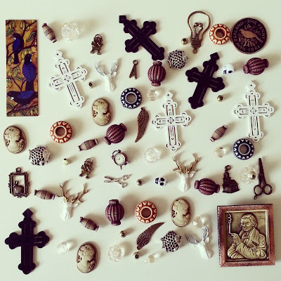 Selection of miniature pictures, vases, crosses and charms laid out on a tabletop.