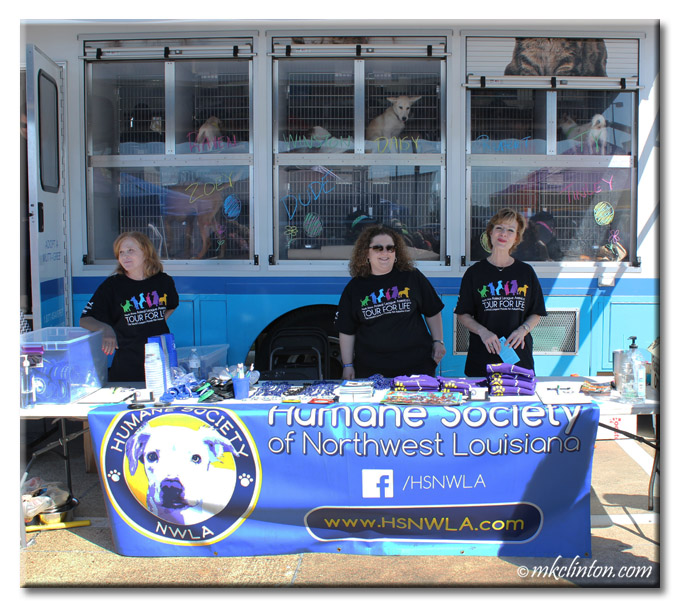 Three women at booth for Tour for Life pet adoption