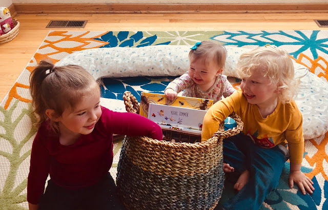Montessori kids reading into summer morning basket for books and activities