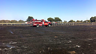 A fire truck in a smoking field after the fire.