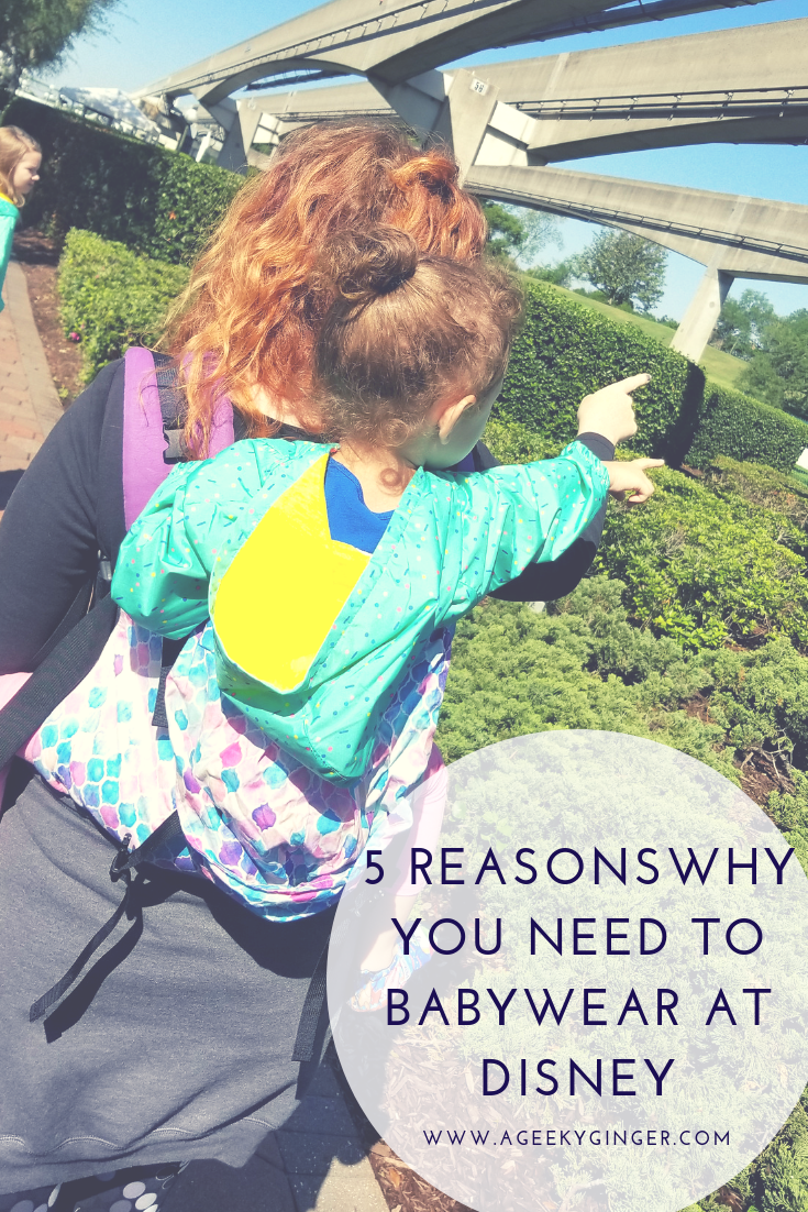 "Curly red haired woman, with her back to the camera, is babywearing her toddler on her back in a purple, blue, and pink soft structured carrier. The mother and toddler are pointing to the Monorail system at Magic Kingdom. Caption reads ""5 Reasons Why You need To Babywear At Disney"""