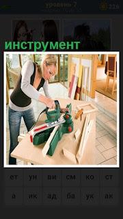 За столом трудится женщина используя инструмент