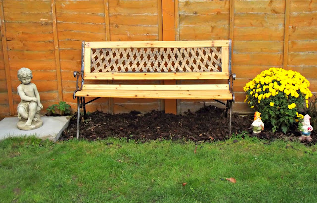 Memorial bench flanked with a cherub and a huge yellow Chrysanthemum