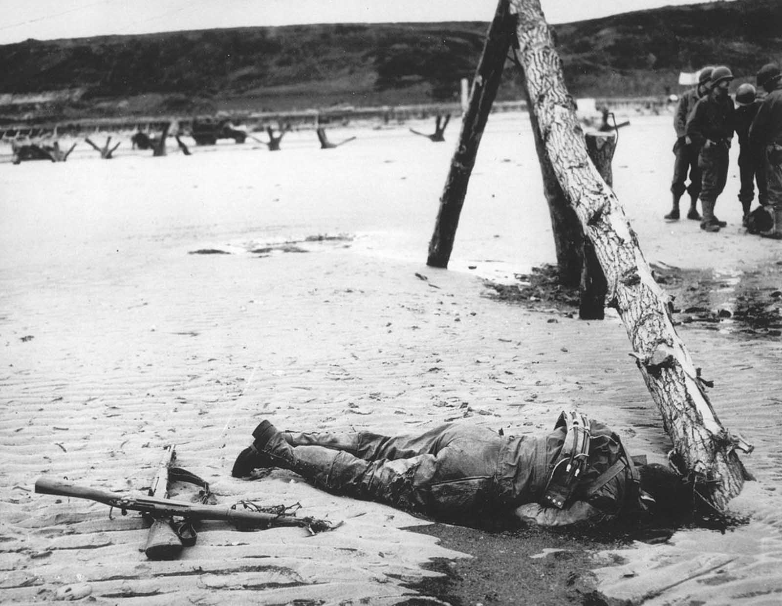 An American soldier, who died in combat during the Allied invasion, lies on the beach of the Normandy coast, in the early days of June 1944. Two crossed rifles in the sand next to his body are a comrade's last reverence. The wooden structure on the right, normally veiled by high tide water, was an obstruction erected by the Germans to prevent seaborne landings.
