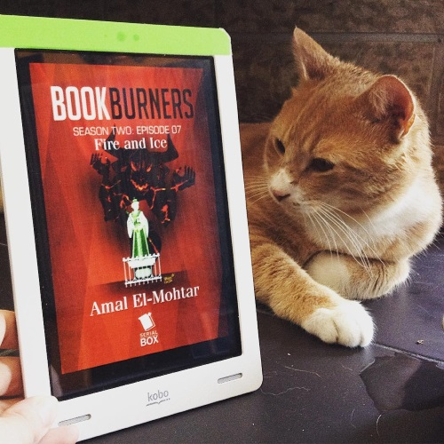 A pale ginger cat, Ollie, lies on some black tiles next to an upright white Kobo with Bookburners Episode 7's red cover on its screen. The cover features a dark demon rising up behind a stylized sculpture of Queen Victoria.