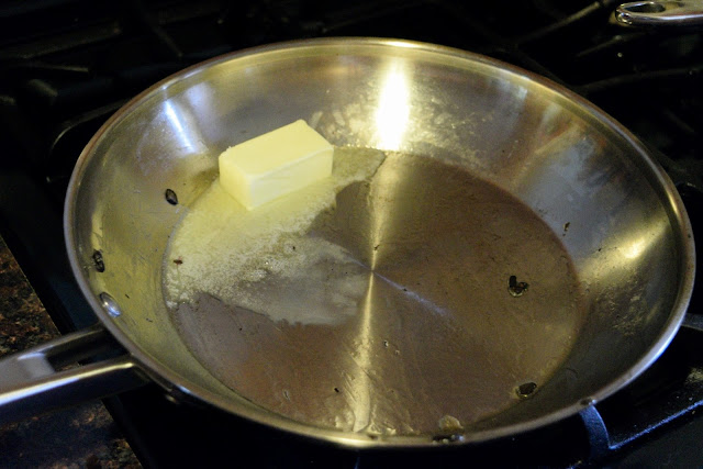 Butter melting in a skillet on the stove.