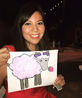 Amber McCrary headshot holding a drawing of a sheep