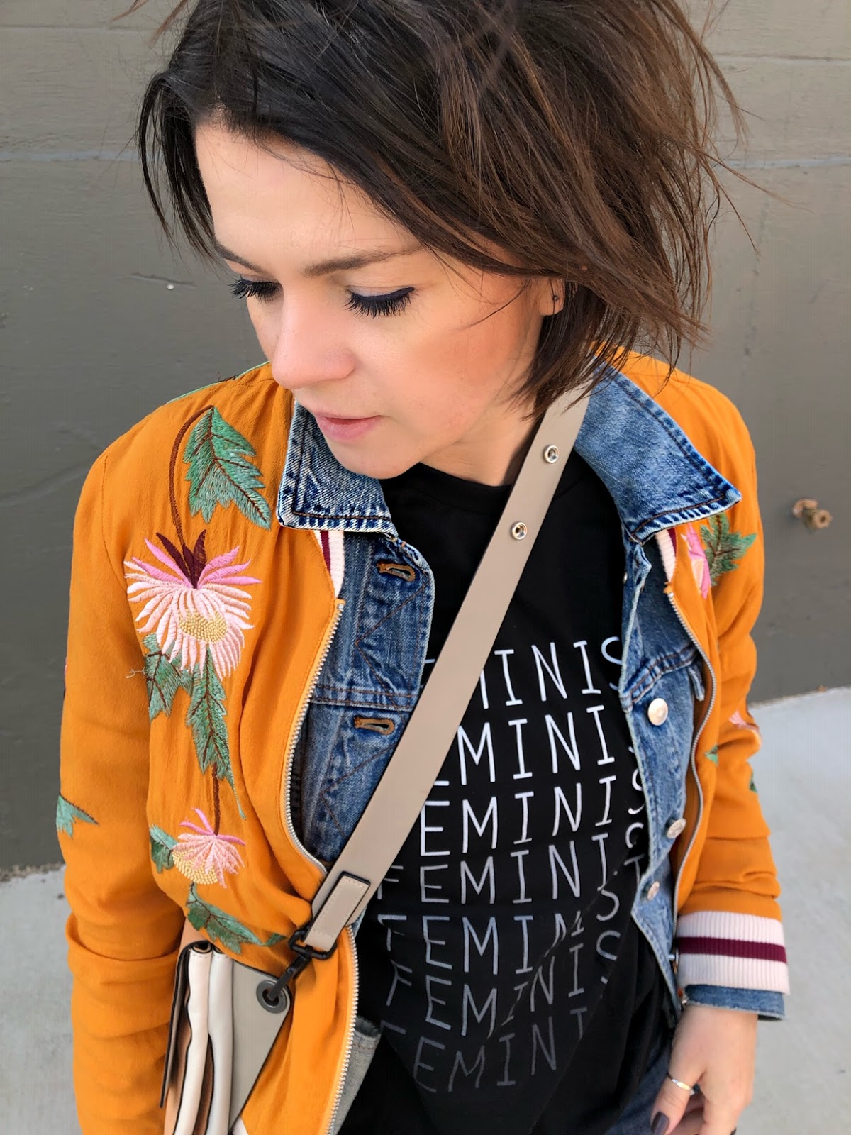 wearing a denim jacket and an orange embroidered bomber jacket
