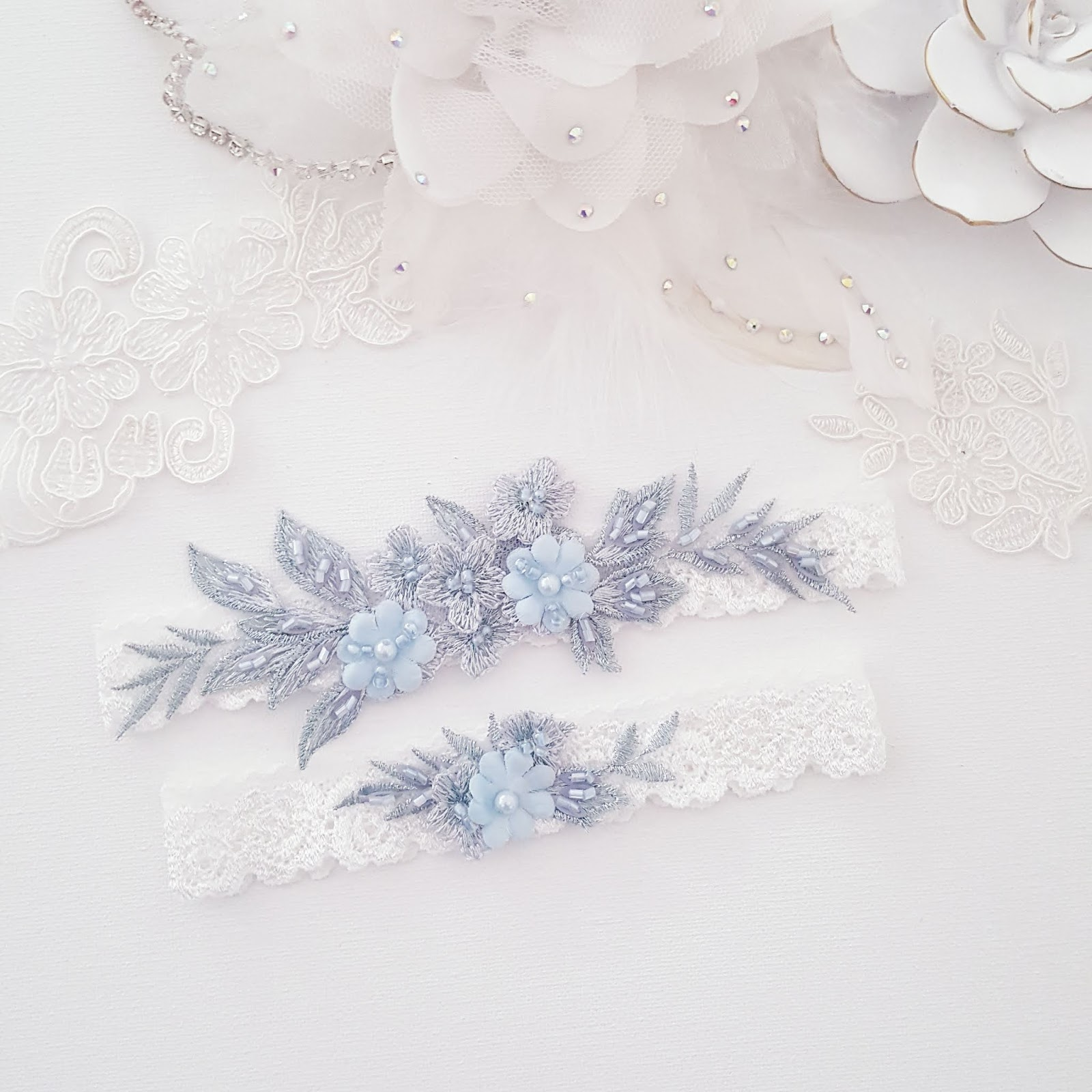 This beautiful handmade bridal garter is adorned with lace applique in a botanical theme, it's the perfect something blue for your wedding. This bridal garter set is one of many wedding accessories from She Wore Flowers.