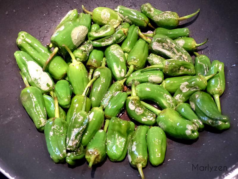 Faites revenir les pimientos del padron dans de l'huile d'olive.