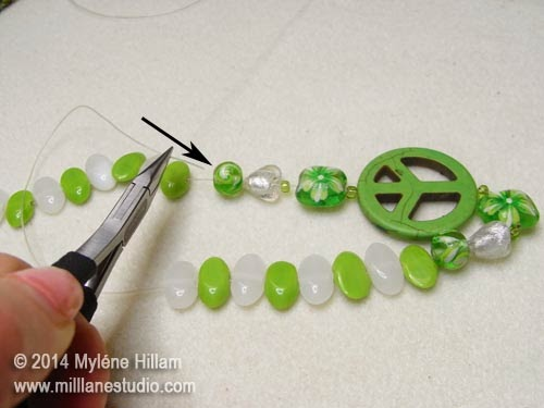 Inserting the elastic back through the first bead
