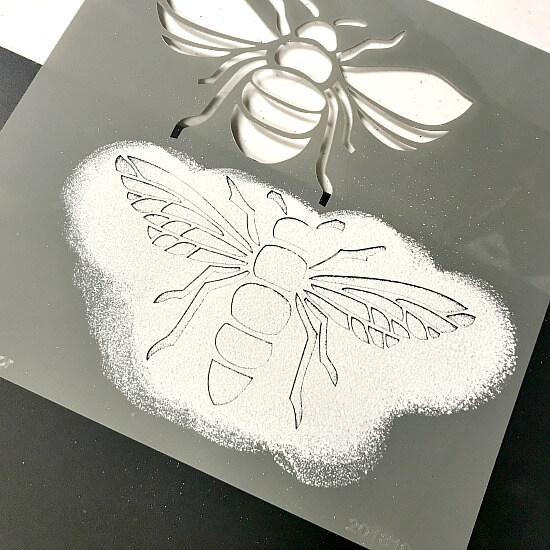 Bee stencil with white paint on a chalkboard