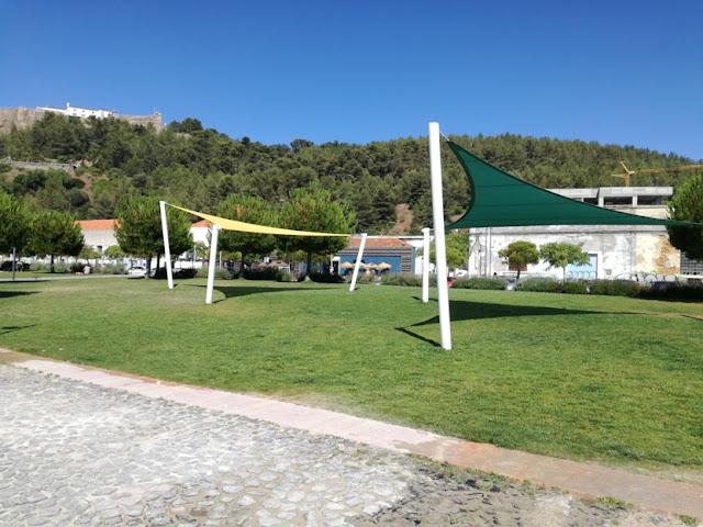 Espaço verdejante com sombra ao lado da praia