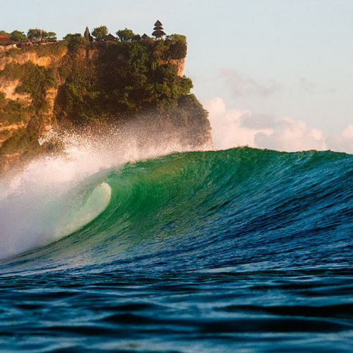 Tinuku Travel Surfing Uluwatu beach riding 8 meters Indian Ocean waves in hidden spots under sacred temple cliffs