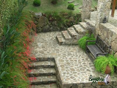 Escada de pedra, com pedra moledo, com o piso de pedra e o banco de madeira.