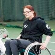 A caucasian young woman with red hair tied back. She is wearing glasses and a black hoodie and is sat in a wheelchair with a tennis racket in one hand.