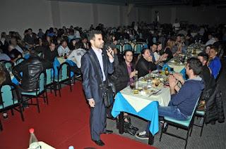 Ο Βαγγέλης Αυγουλάς μιλάει στο κοινό αφού έχουν ανάψει τα φώτα σε δείπνο στην Αθήνα