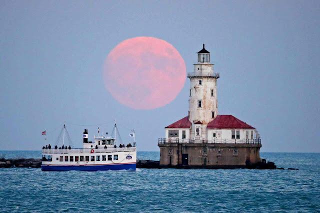 Mặt Trăng vừa mọc vào buổi chiều cùng với Hải đăng Chicago tại bang Illinois, phía tây Hoa Kỳ. Hình ảnh: Jerry Lai/DDP USA/Barcroft Images.