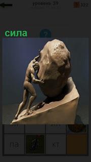 человек с большой силой толкает камень на скульптуре