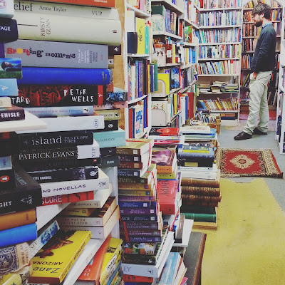 Interior of a second-hand bookshop, with full shelves and stacks of books on the counter.