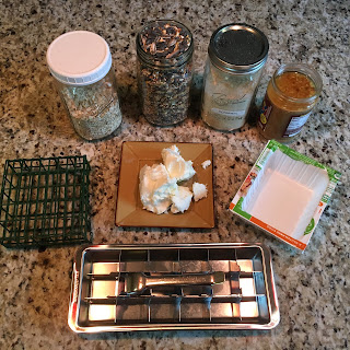 Photo of supplies used to make suet feeder, including suet feeder cage, quart jars of oats, bird seed, and cornmeal, a blob of vegetable shortening, empty plastic tofu container, and a stainless steel ice cube tray. https://trimazing.com/