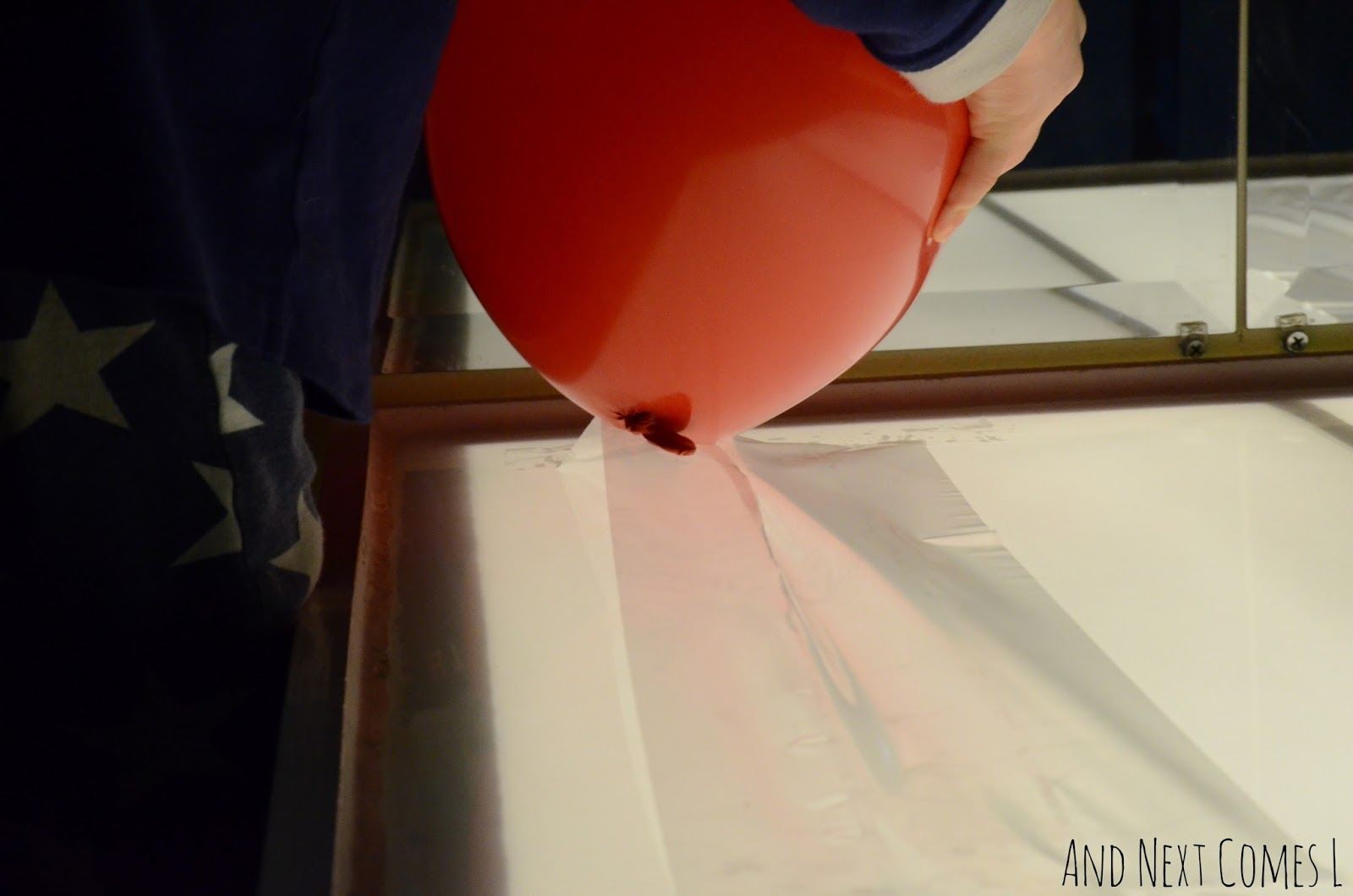 Pulling balloons off of a sticky light table from And Next Comes L