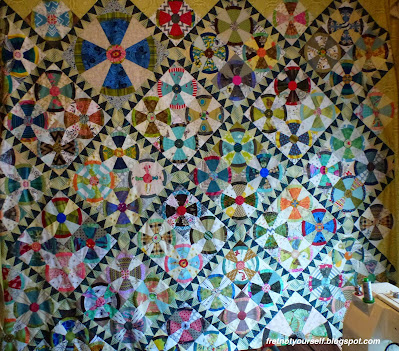Quilt in shades of blue, chartreuse, green,  brown, red, grey, orange, pink