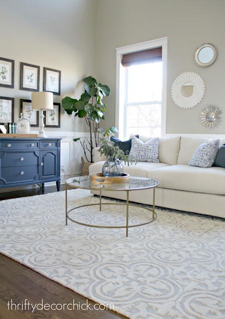 Gallery wall, blue dresser, light sofa living room