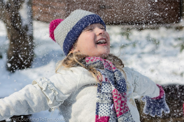 A young girl in hat, scarf, gloves and jumper who has just thrown snow up in the air so it is showering down on her