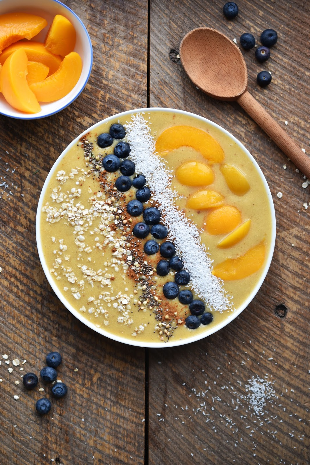 Peach Pie Smoothie Bowl - the New Year's #healthy answer to peach pie, with canned peaches (handy in winter!), a touch of decadent coconut cream & toppings like coconut, blueberries, oats & cinnamon. #vegan #glutenfree #bowls #smoothies #smoothiebowls