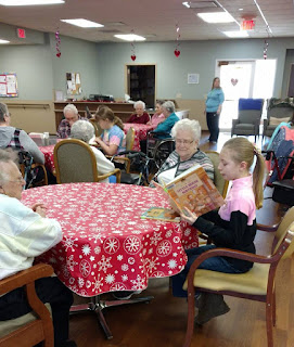 a girl reads a picture book aloud while sitting at a table with 2 senior citizens, other reading groups are in the background