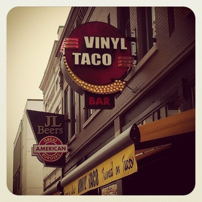 Photograph of a round sign that reads 'Vinyl Taco.' It protrudes from a grey-painted brick building, an awning with further taco slogans directly below it.