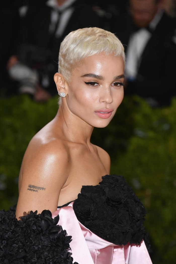 Image of hollywood actress zoe kravitz wearing a satin gown with short blonde hair on the red carpet