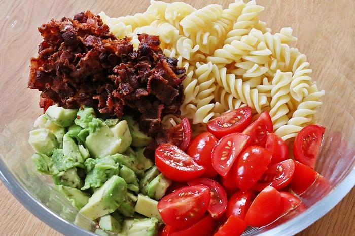 lauwarmer Tomaten-Bacon-Nudelsalat mit Avocado Dressing & scharfen Hähnchen Teilen
