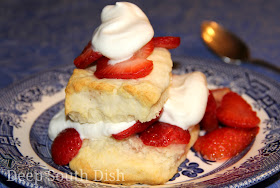 Sugar macerated strawberries served over homemade cream biscuits with homemade whipped cream.