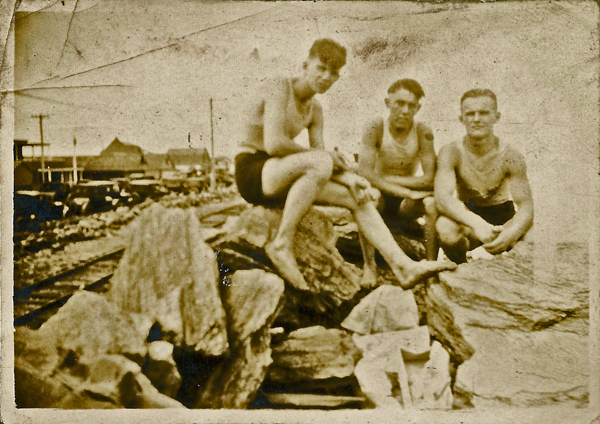 Three unidentified young men take a break from the beach to lounge on the rocks. There are railroad tracks and old cars parked behind them. 1920's? From photo album of Estelle Karvoius, privately held by E. Ackermann, 2016.