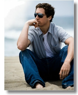 Caucasian male with jeans sitting on beach thinking wearing sunglasses