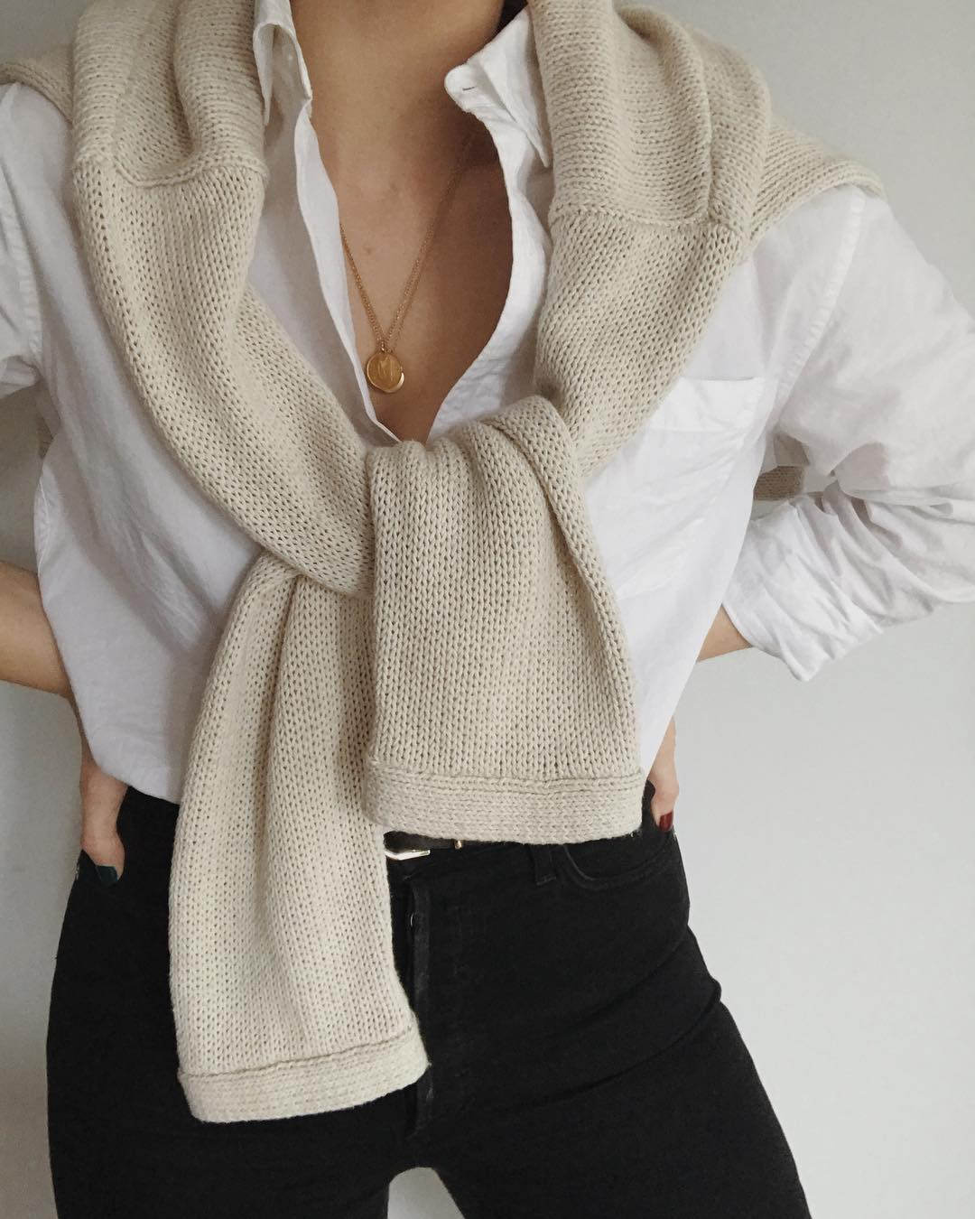 Casual-Chic Fall Outfit Inspiration — Beige Sweater Tied Over the Shoulders, White Shirt, Black Jeans, Coin Necklaces